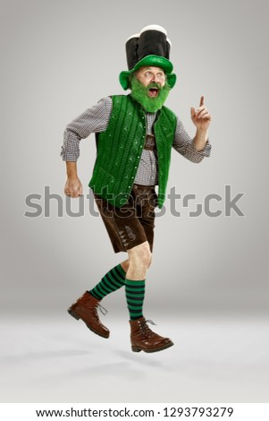 A smiling happy senior man in a leprechaun hat with beard running at studio. He celebrates St. Patrick's Day. The celebration, festive, beer, holiday, alcohol, party concept #1293793279