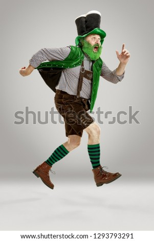 A smiling happy senior man in a leprechaun hat with beard running at studio. He celebrates St. Patrick's Day. The celebration, festive, beer, holiday, alcohol, party concept