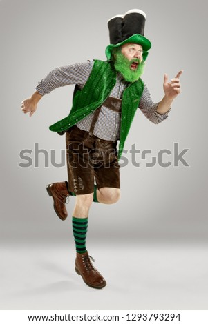 A smiling happy senior man in a leprechaun hat with beard running at studio. He celebrates St. Patrick's Day. The celebration, festive, beer, holiday, alcohol, party concept #1293793294