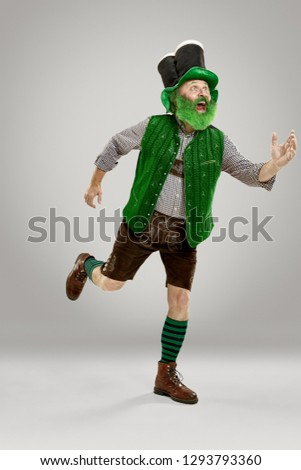 A smiling happy senior man in a leprechaun hat with beard running at studio. He celebrates St. Patrick's Day. The celebration, festive, beer, holiday, alcohol, party concept #1293793360