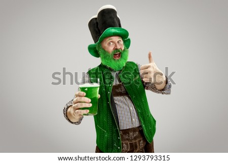 A smiling happy senior man in a leprechaun hat with green beer at studio. He celebrates St. Patrick's Day. The celebration, festive, beer, holiday, alcohol, party concept