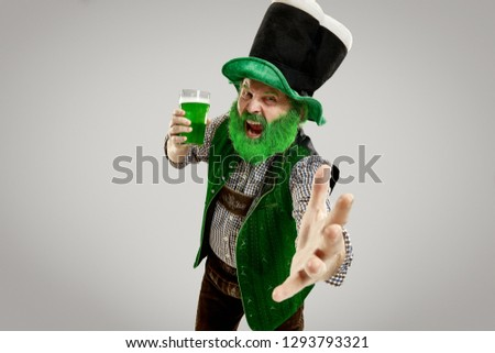 A smiling happy senior man in a leprechaun hat with green beer at studio. He celebrates St. Patrick's Day. The celebration, festive, beer, holiday, alcohol, party concept #1293793321