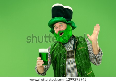 A smiling happy senior man in a leprechaun hat with green beer at studio. He celebrates St. Patrick's Day. The celebration, festive, beer, holiday, alcohol, party concept #1299295942