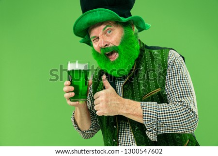 A smiling happy senior man in a leprechaun hat with green beer at studio. He celebrates St. Patrick's Day. The celebration, festive, beer, holiday, alcohol, party concept #1300547602