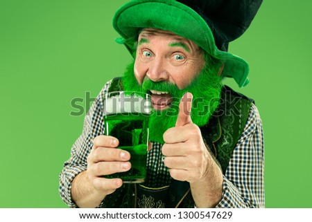 A smiling happy senior man in a leprechaun hat with green beer at studio. He celebrates St. Patrick's Day. The celebration, festive, beer, holiday, alcohol, party concept #1300547629
