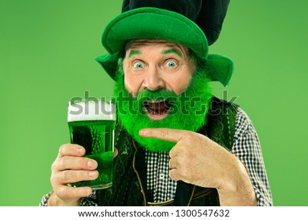 A smiling happy senior man in a leprechaun hat with green beer at studio. He celebrates St. Patrick's Day. The celebration, festive, beer, holiday, alcohol, party concept #1300547632