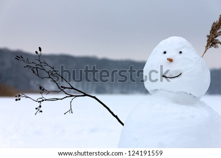 A smiling happy snowman raises the twig it has for an arm in greeting before the background of a frozen lake and forest.