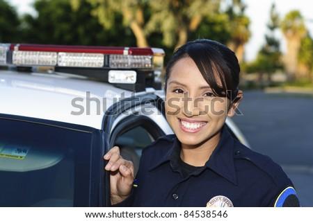 a smiling Hispanic police officer next to her patrol car. Stock fotó ©