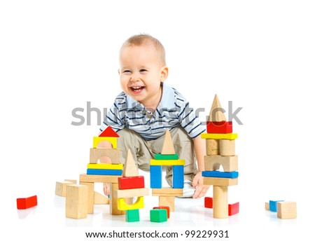 A smiling little boy is building a toy block sitting on the floor