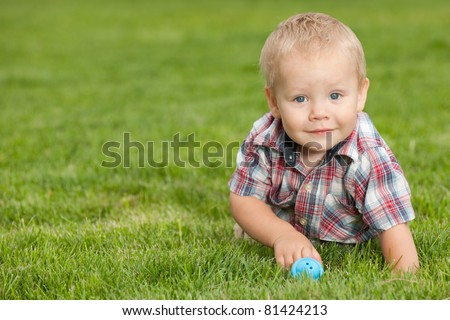 A smiling little boy is playing on the green grass