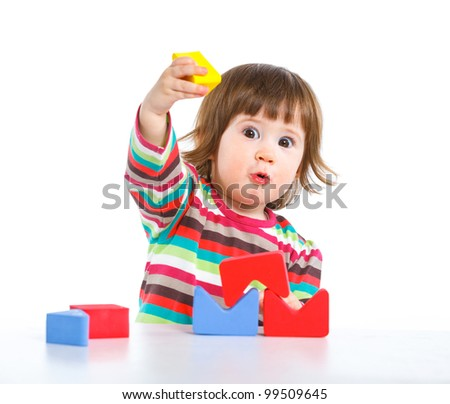 A smiling little girl is building a toy block. Isolated on white background