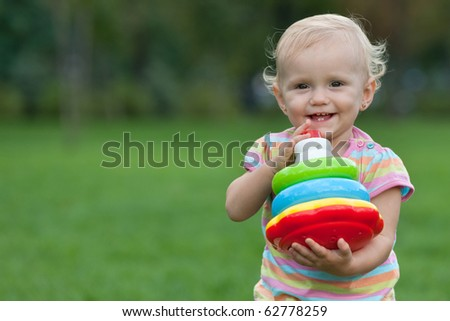 A smiling little girl is holding a toy pyramid in her hands while walking out in the park