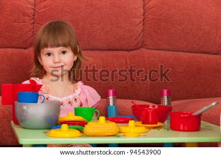 A smiling little girl is playing at the table