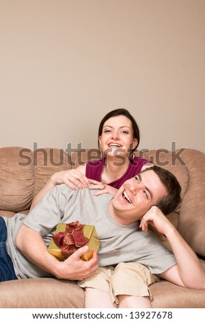 A smiling man holding a gift box lying on a smiling woman's lap on sofa.  Vertically framed shot.