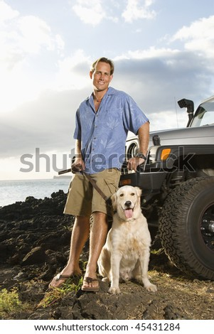 A smiling man leans against his SUV at the beach as he holds his dog's leash and looks at the camera. Vertical format.