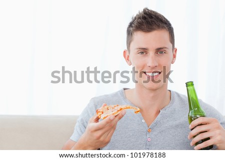 A smiling man looking at the camera as he eats pizza and holds some beer