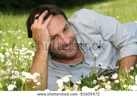 A smiling man lying in a garden amid flowers.