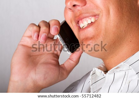 A smiling man on a mobile phone