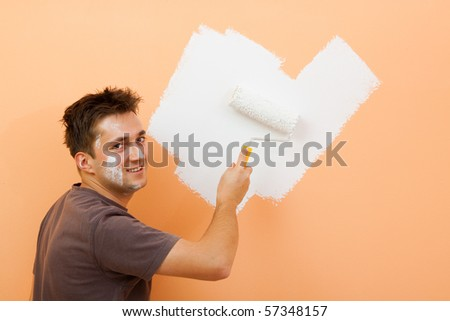A smiling man painting the  orange wall
