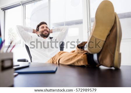 A smiling man relaxing in the office with legs crossed on the desk