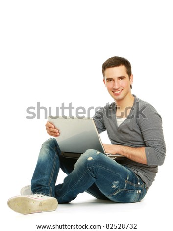 A smiling man sitting on the floor with a laptop, isolated on white