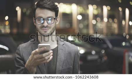 A smiling man wearing eyeglasses is holding scrolling texting in his cellphone. A smiling man calls for a taxi in an app. #1062243608