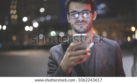 A smiling man wearing eyeglasses is holding scrolling texting in his cellphone. A smiling man calls for a taxi in an app. #1062243617