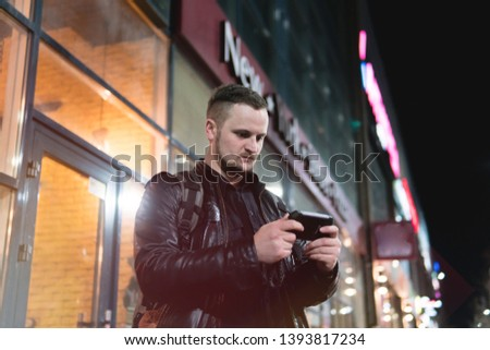 A smiling man wearing in black jacket, is holding scrolling texting in his cellphone. A smiling man calls for a taxi in an app. online, networking, outdoor night city street #1393817234