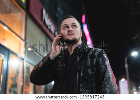 A smiling man wearing in black jacket, is holding scrolling texting in his cellphone. A smiling man calls for a taxi in an app. online, networking, outdoor night city street #1393817243