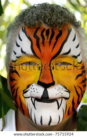 A smiling man who's face is painted like a tiger.