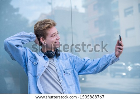 A smiling man with glasses and headphones taking a picture of himself with his smartphone. Concept of technological youth. Portrait