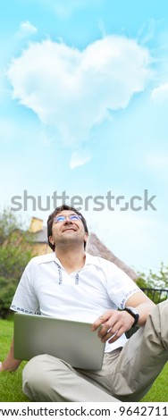 A smiling man with laptop outdoor sitting at his backyard and looking up to the cloud of heart shape overhead