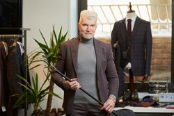 A smiling mature man with gray hair and a sporty physique is holding a fiber carbon cane with two hands in a clothing store. A male customer with a beard wears a suit in a boutique.