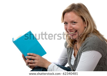 A smiling mid thirties woman with long blonde hair sitting and reading a book.