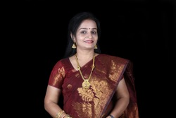 A smiling middleaged Indian woman in a traditional saree, on black studio background.