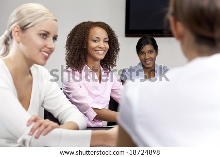 A smiling mixed race African American businesswoman and her three colleagues taking part in a happy business meeting, the focus is on the African American woman.