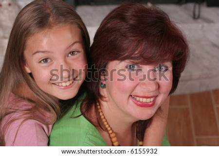 a smiling mother and a daughter sitting on the floor