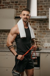A smiling muscular man with a white towel on the shoulders is posing with pull elastic rope in his apartment. The athletic guy with tattoos on his forearms is demonstrating his sporty physique at home