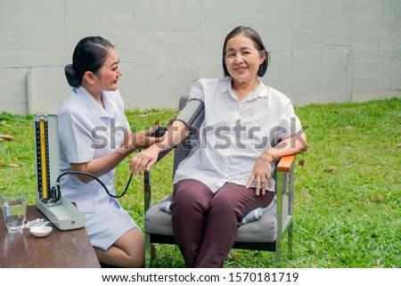 A Smiling nurse checking senior patient's blood pressure. An elderly woman in a nursing house. Nursing home, Hospital, health, care, nurse Concept.