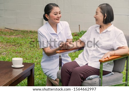 A Smiling nurse holding hands with supporting  an elderly woman  in a nursing house. Nursing home, Hospital, health, care, nurse Concept.