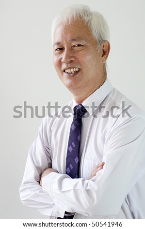 a smiling old asian ethnic businessman with plain background