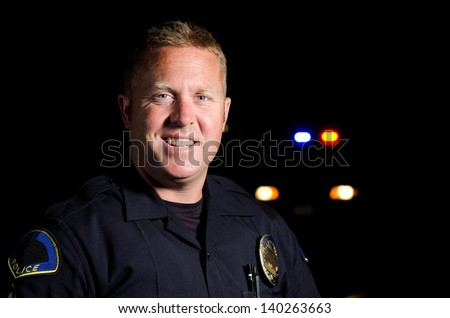 A smiling police officer at night with his patrol car in the background.