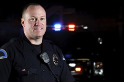 a smiling police officer in the night in front of his patrol unit.