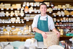 A smiling salesman in an apron holding a big cheese slab and standing at a counter in a cheese shop.