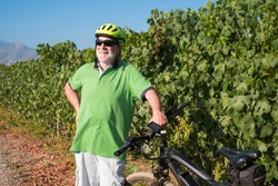 A smiling senior man with white hair and beard standing close to his e bike. Bunches of grapes behind him. Retired elderly caucasian people.Green vineyard in background.
