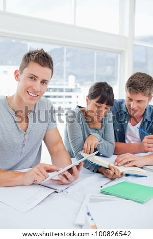A smiling student using a tablet looks into the camera as his friends use a book to find the answer