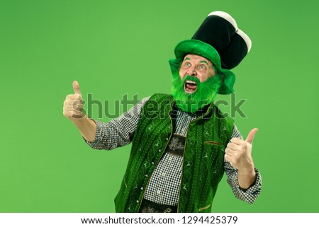 A smiling surprised happy senior man in a leprechaun hat with beard at green studio. He celebrates St. Patrick's Day. The celebration, festive, beer, holiday, alcohol, party, human emotions concept #1294425379