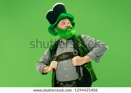 A smiling surprised happy senior man in a leprechaun hat with beard at green studio. He celebrates St. Patrick's Day. The celebration, festive, beer, holiday, alcohol, party, human emotions concept #1294425406