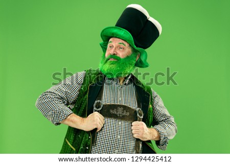 A smiling surprised happy senior man in a leprechaun hat with beard at green studio. He celebrates St. Patrick's Day. The celebration, festive, beer, holiday, alcohol, party, human emotions concept #1294425412