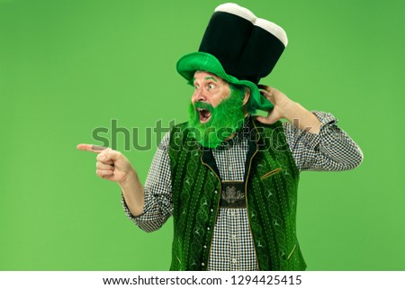 A smiling surprised happy senior man in a leprechaun hat with beard at green studio. He celebrates St. Patrick's Day. The celebration, festive, beer, holiday, alcohol, party, human emotions concept #1294425415